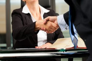 Mature female lawyer or notary with client in her office - hands